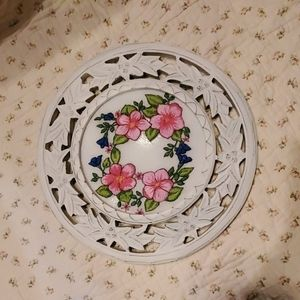 An embroidered picture of flowers in a  round wood